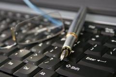 Pen on a laptop Royalty Free Stock Photos
