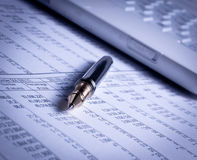 Pen and laptop on charts Stock Image