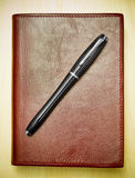 Pen on leather journal. Black pen on red leather journal on desk Royalty Free Stock Image