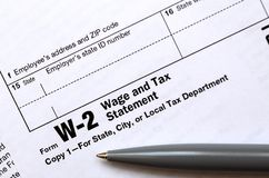 The pen lies on the tax form W-2 Wage and Tax Statement. The tim stock photography