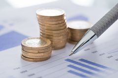 Pen with line and coins graphs on desk Stock Photo