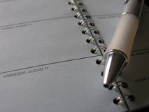Pen Lying Across Open Page av dagtidmätaren Royaltyfria Foton