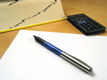 Pen lying on blank paper II. Blank paper and pen infront of calculator and book Royalty Free Stock Image