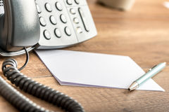 Pen lying on blank white note cards next to a landline telephone. On a wooden office desk. Copy space ready for your notes or text Royalty Free Stock Image