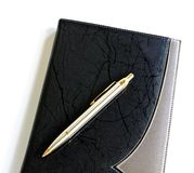 Pen lying on a notebook. Over white Royalty Free Stock Photography