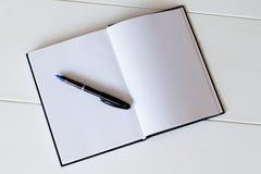 Pen lying on opened clear notepad. Horizontal indoors shot Stock Image