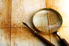 Pen and magnifier. On old textured paper royalty free stock images