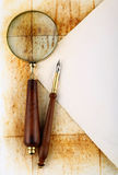 Pen and magnifier. On old textured paper royalty free stock image