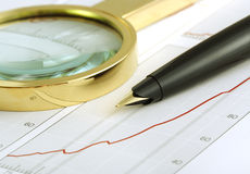 Pen and magnifying glass focusing on chart. Royalty Free Stock Images