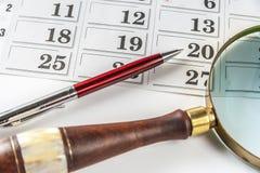 Pen And Magnifying Glass On-Kalender Lizenzfreie Stockfotografie