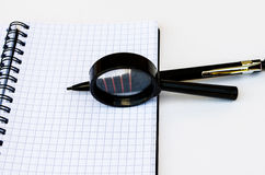 Pen and magnifying glass lie on the notebook in the box Stock Photo