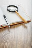 Pen and magnifying glass on notebook Stock Photo