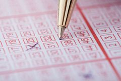 Pen marking numbers on lottery ticket Stock Photo