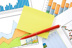 Pen and memo over charts Stock Photography