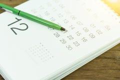 Pen met de close-up van de kalenderpagina op houten lijst stock foto's
