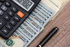 Pen, money and calculator on desk.  Royalty Free Stock Photography