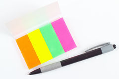 Pen and multicolored stickers on white desktop Stock Images