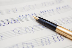 Pen and music sheet with handwritten notes Stock Photos
