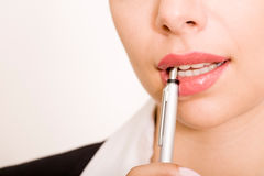 Pen near mouth Royalty Free Stock Image