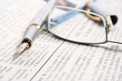 PEN ON NEWSPAPER WITH GLASSES Stock Images