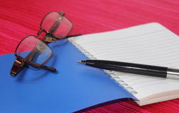 Pen on note book with eye glasses Royalty Free Stock Photo