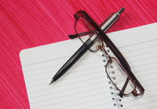 Pen on note book with eye glasses. On pink background royalty free stock photo