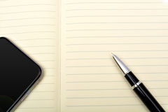 Pen with note book and smart phone Stock Images
