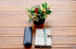 Pen on note book and Spectacles glasses with plastic flower Royalty Free Stock Photo