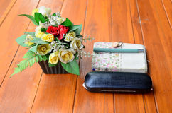 Pen on note book and Spectacles glasses with plastic flower Royalty Free Stock Image