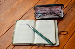 Pen on note book and Spectacles glasses Stock Image