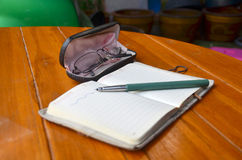 Pen on note book and Spectacles glasses Stock Photo