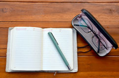 Pen on note book and Spectacles glasses Stock Photography