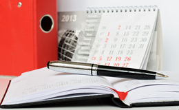 Pen on a notebook. Pen on an opened notebook with a calendar Royalty Free Stock Photos