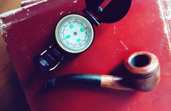 Pen and notebook b. Photograph of a compass, a pipe and some old books on a wood table stock photography