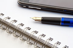 Pen, notebook and cell phone Royalty Free Stock Photography