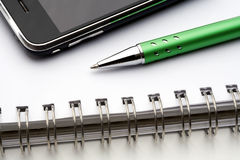 Pen, notebook and cell phone Royalty Free Stock Image
