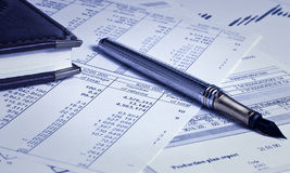 Pen and notebook on charts Stock Photos
