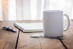 Pen and notebook with coffee cup on wooden Stock Images