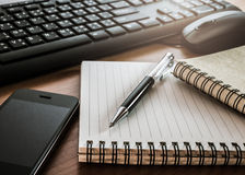 Pen on notebook with computer keyboard, mouse and cell phone Stock Photo