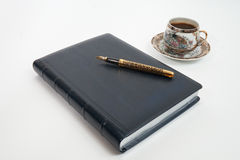 Pen on notebook and cup Stock Photography