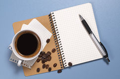 Pen and notebook. With cup of coffee on blue desk, top view Royalty Free Stock Image