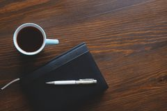 Pen, notebook or diary, a mug of tea or coffee on a wooden table. Free space for text. Management concept, business, making a plan royalty free stock photos