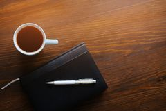 Pen, notebook or diary, a mug of tea or coffee on a wooden table. Free space for text. Management concept, business, making a plan stock photo