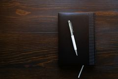 Pen, notebook or diary on a wooden table. Free space for text. The concept of office, education, business, making a plan for the royalty free stock photography