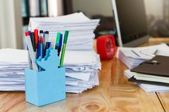 Pen with notebook and documents on wooden table in home office. Pen with notebook and documents on wooden table in home office at morning royalty free stock images