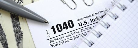 The pen, notebook and dollar bills is lies on the tax form 1040 stock images