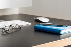 Pen on Notebook and Eyeglasses by a Computer on Office Table Stock Photography