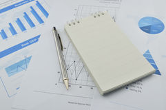 Pen and notebook on financial chart and graph Royalty Free Stock Photography