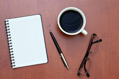 Pen, notebook and glasses with coffee Royalty Free Stock Image
