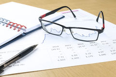Pen, notebook, glasses and financial report Royalty Free Stock Images